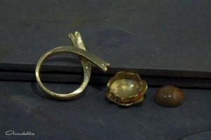 Kovácsolt gyűrűalap, szirmocskás foglalat, és megkövesedett fa kaboson